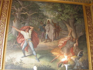 Hagens Mord an Siegfried (Quelle: https://de.wikipedia.org/wiki/Nibelungensage#/media/File:Munich_Nibelung_Halls-Murder_of_Siegfried.jpg